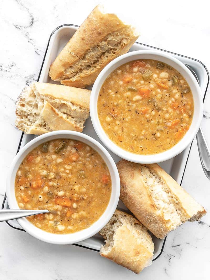 Overhead view of two bowls of slow cooker white bean soup on a white tray with torn pieces of baguette on the sides