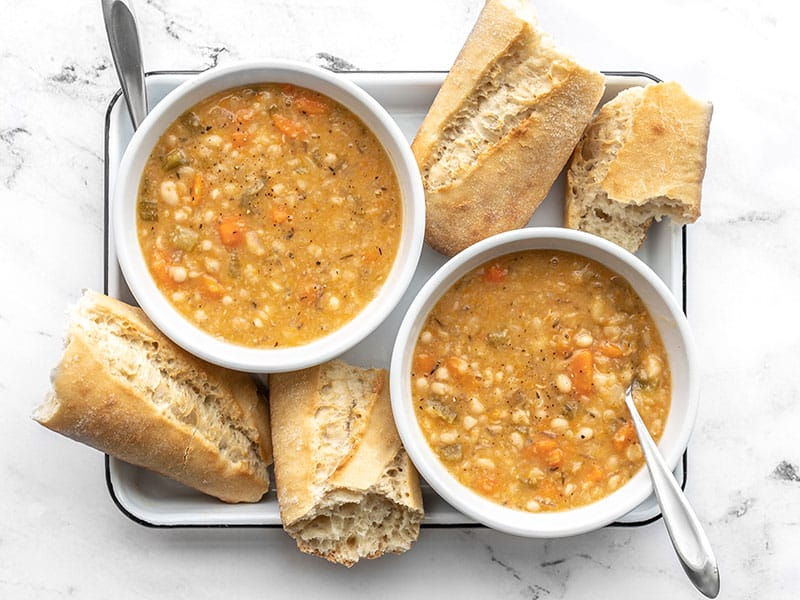 Overhead view of two bowls of slow cooker white bean soup with pieces of baguette on the sides