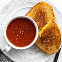 Tomato herb soup in a mug on a plate with grilled cheese