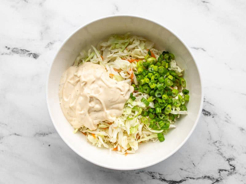 Coleslaw mix with green onions and dressing in a bowl