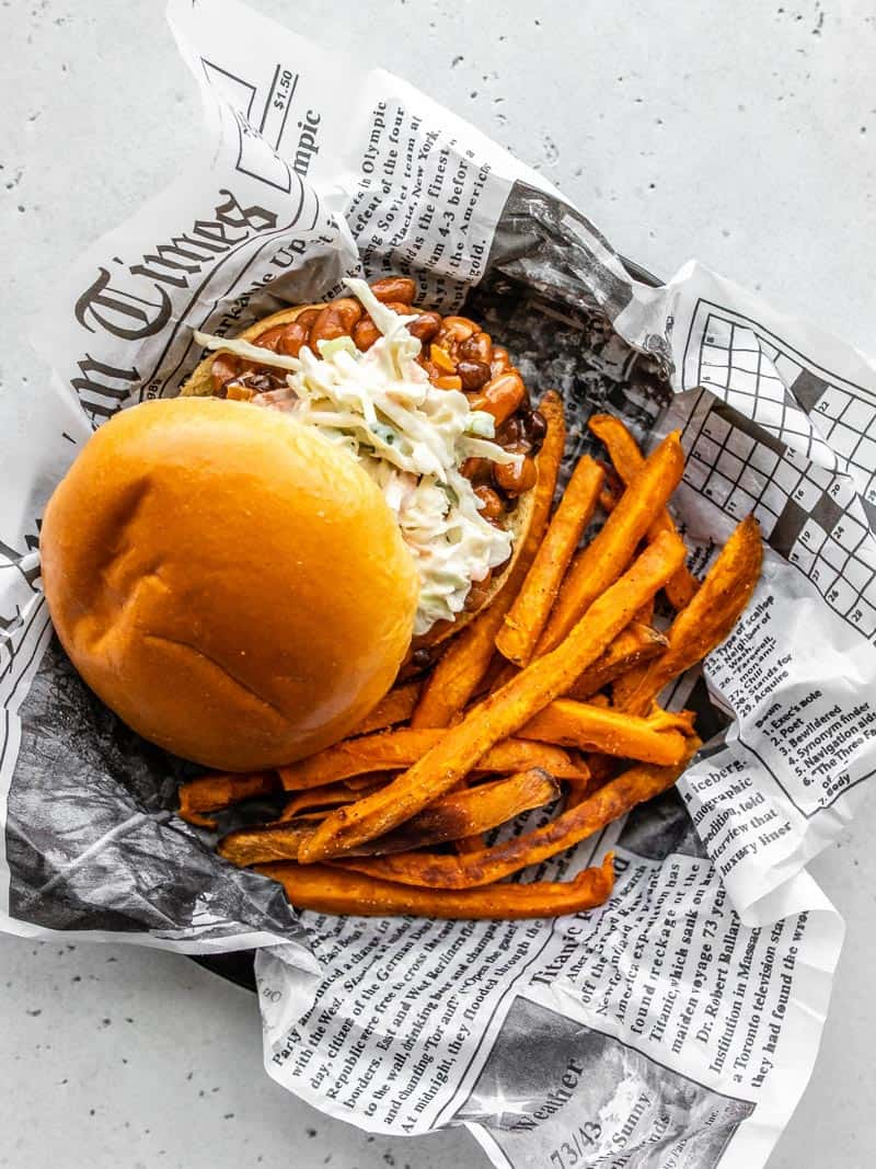 Overhead view of a plate covered with newsprint with one BBQ Bean Slider and some sweet potato fries