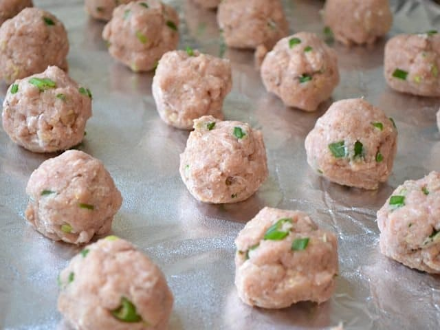 Meatball mix formed into meatballs and placed on baking sheet