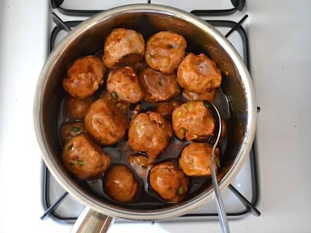 Cooked Meatballs added to pot of glaze on stovetop