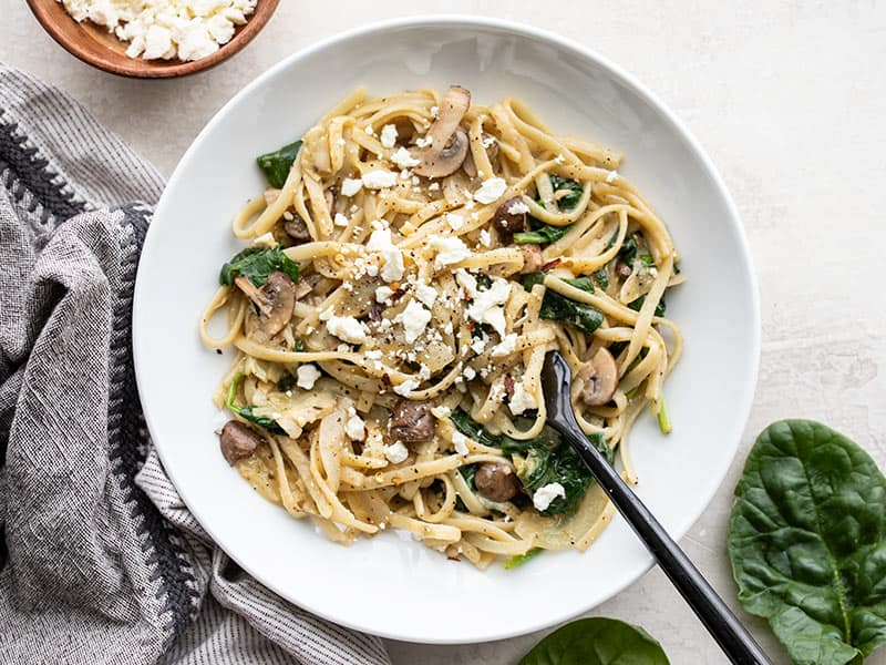 A shallow bowl full of Spinach and Artichoke One Pot Pasta with spinach and feta on the sides.