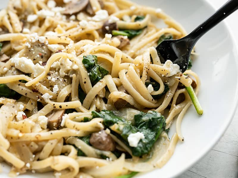 Close up of Spinach and Artichoke One Pot Pasta on the plate being twirled around a fork