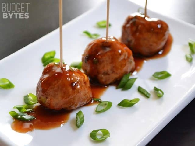 Three Turkey Sriracha Meatballs with toothpicks plated on a square plate and garnished with green onions