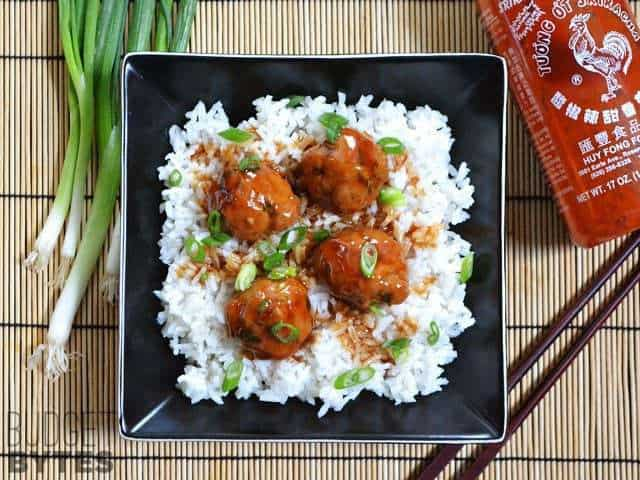 Top view of a bowl of Turkey Sriracha Meatballs over white rice with chopsticks and a bottle of Siracha on the side