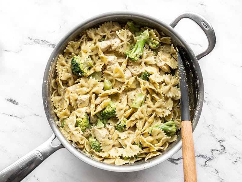 Finished creamy pesto pasta with chicken and broccoli in the skillet with a spatula