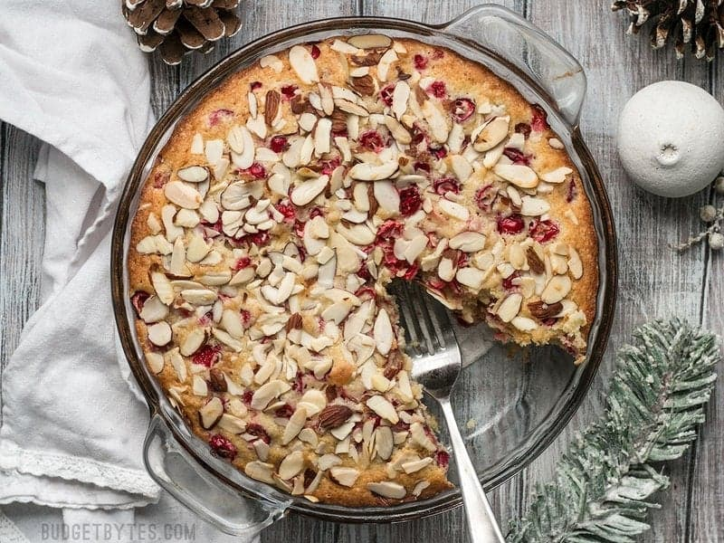 Top view of baked Cranberry Almond Cake with one slice removed