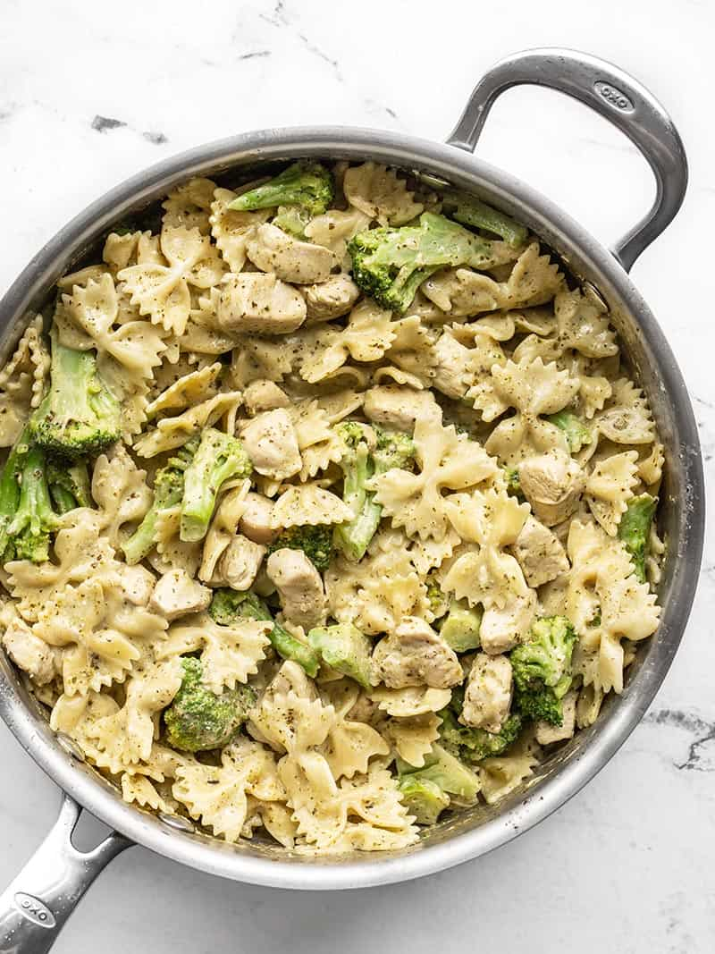 Creamy pesto pasta with chicken and broccoli in the skillet, viewed from above
