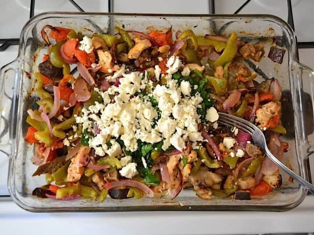 Parsley and Feta mixed into veggies and chicken in baking dish
