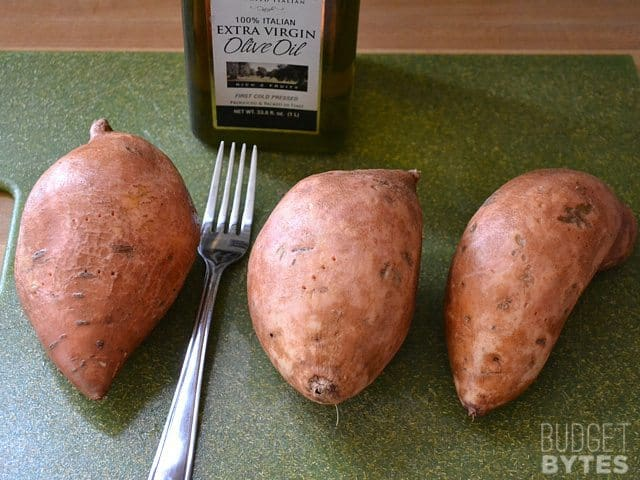 three sweet potatoes with fork to prick before cooking
