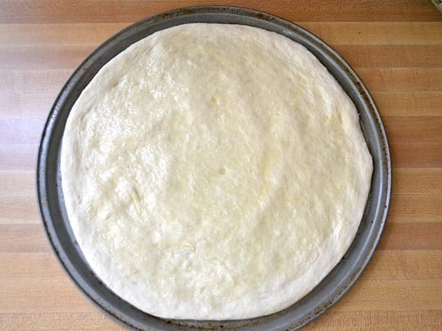 Oiled and rolled dough shaped into circle and placed on pizza pan