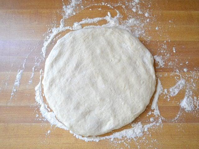 Pizza dough on floured counter top