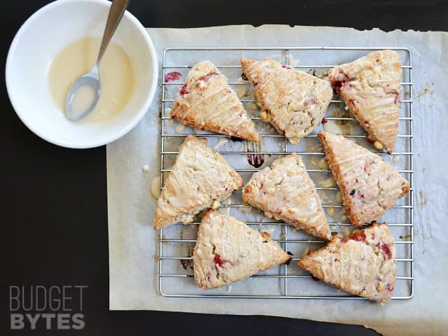 Strawberry White Chocolate Scones on cooling rack with a bowl of glaze on the side