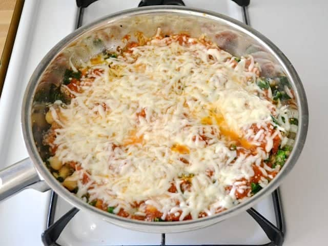 shredded cheese sprinkled over top of dish in skillet and melted