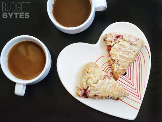 Top view of two Strawberry White Chocolate Scones on a heart shaped plate with two cups of coffee on the side