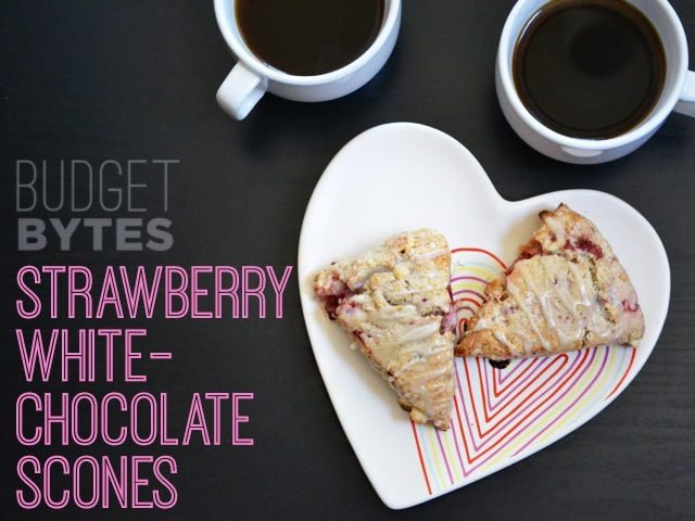 Two Strawberry White Chocolate Scones on a heart shaped plate, with two cups of coffee in the background