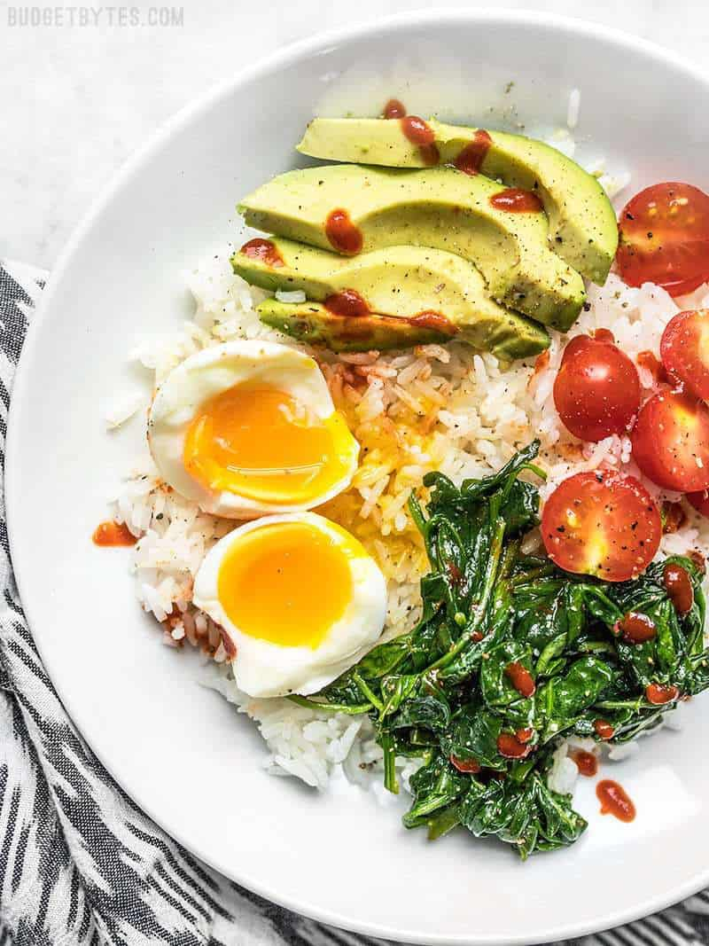 Breakfast bowl with perfectly cooked soft boiled eggs, spinach, avocado, tomato, rice, and sriracha.