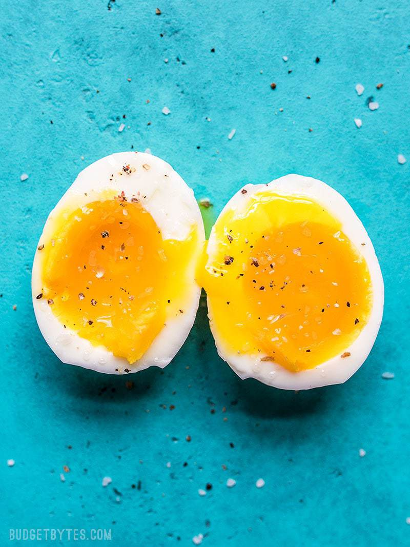 Perfectly cooked soft boiled eggs cut open and sprinkled with salt and pepper.