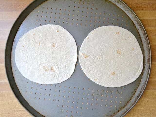 Two tortillas placed on pizza pan
