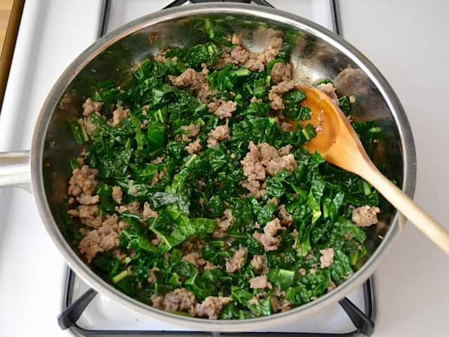 chopped kale added to cooked sausage in skillet