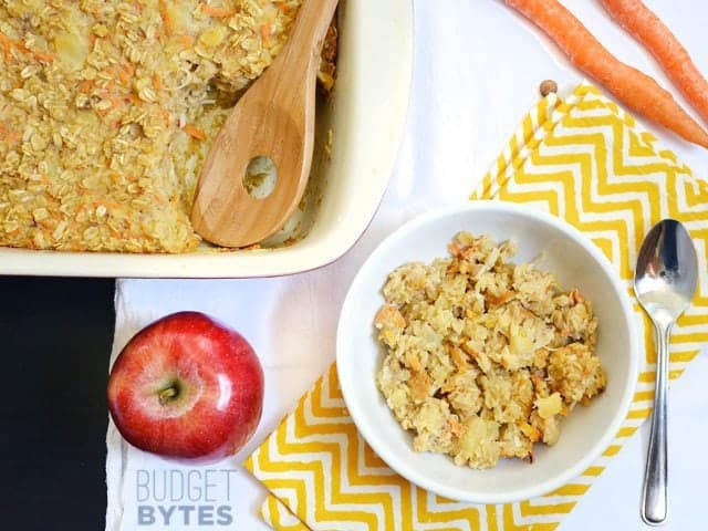 Top view of a bowl of Morning Glory Baked Oatmeal with full pan of oatmeal, an apple and a spoon on the side