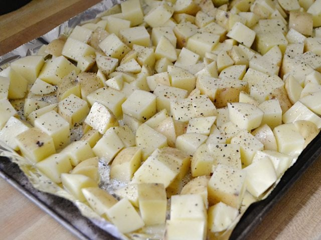 Cubed potatoes spread on baking sheet and seasoned, ready to bake