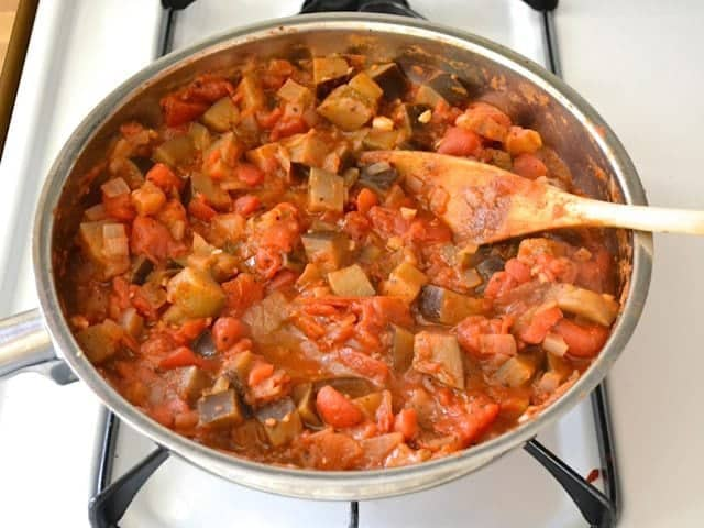 Simmered Sauce mixture in skillet with wooden spoon