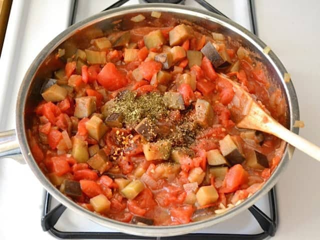 Tomatoes and seasonings added to skillet of other ingredients