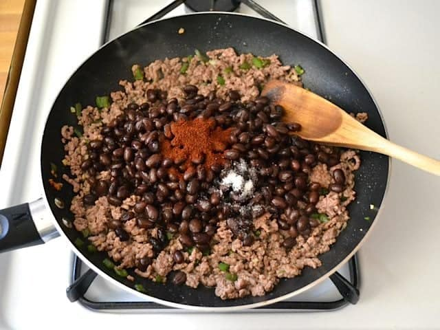 Beans and Seasoning added to other ingredients in skillet