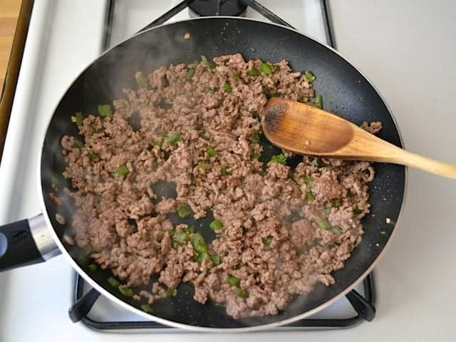 Ground beef added to jalapeño and garlic in skillet and browned