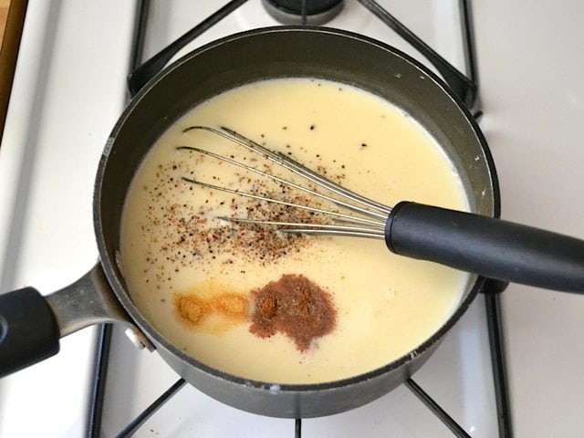 Milk and seasoning added to other sauce ingredients in pan and whisked in