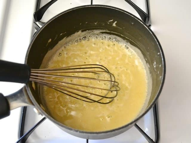 Sauce ingredients in pan with whisk