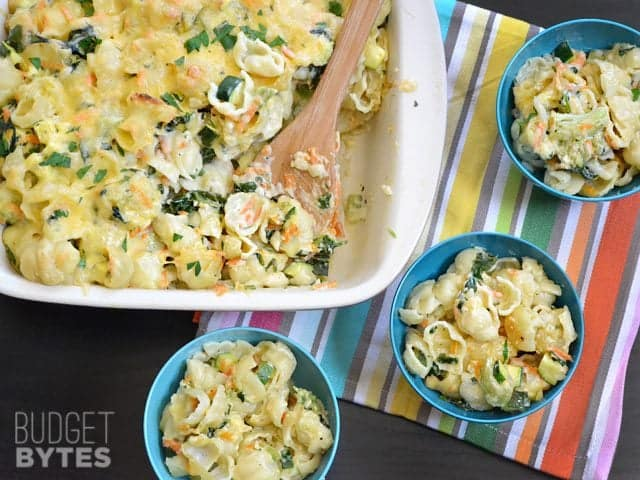 Casserole dish of Vegetable Alfredo Pasta Bake with three small bowls served up