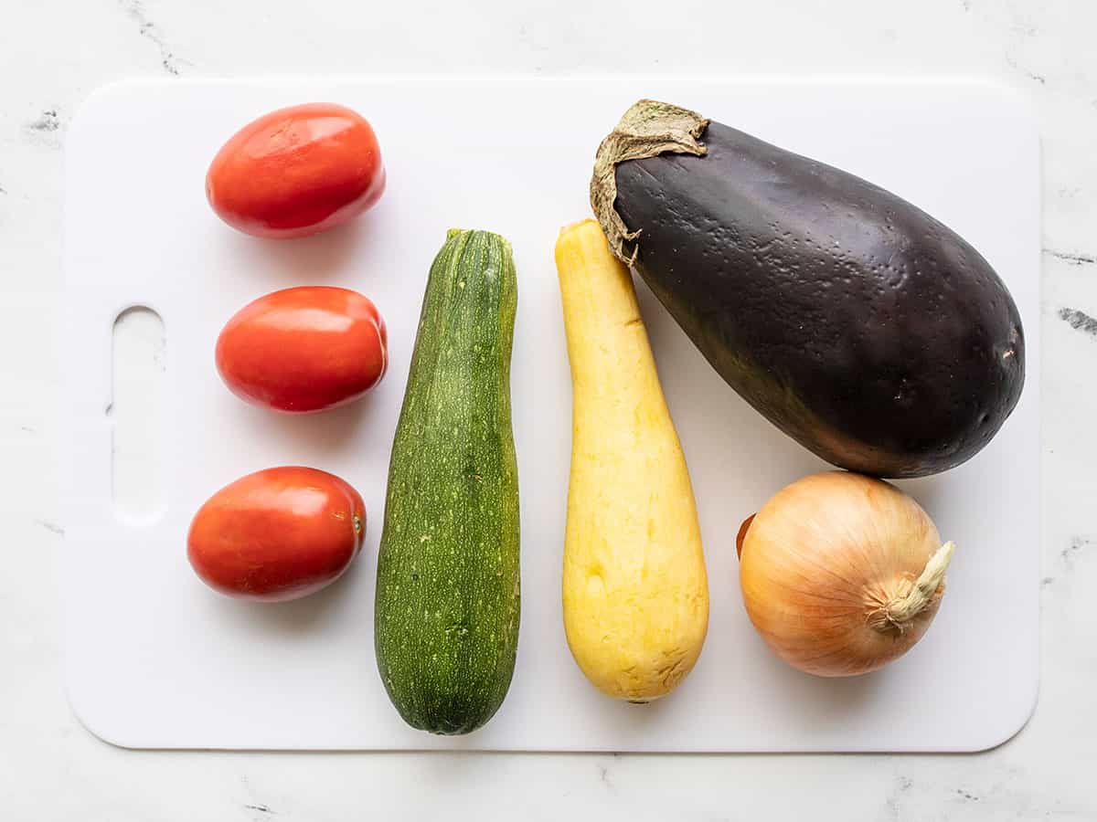 Eggplant, onion, squash, and tomatoes whole on a cutting board