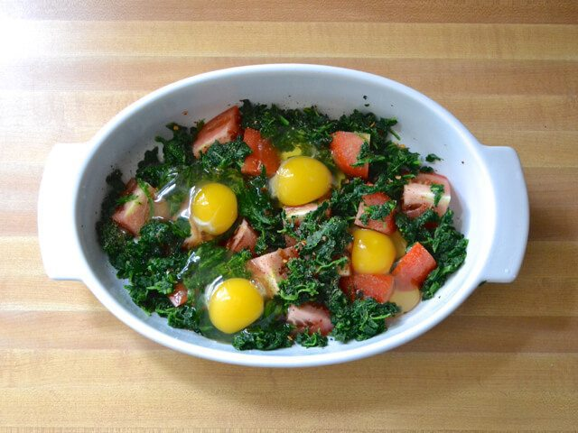 Four eggs cracked in casserole dish over spinach and tomatoes