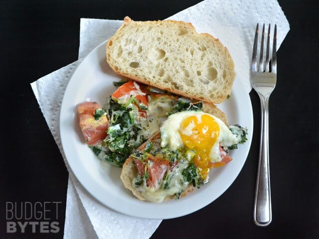 Top view of a plate of Baked Eggs with Tomatoes and Spinach, with a side of bread. Fork and napkin on the side