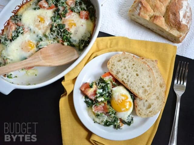 Top view of Baked Eggs with Spinach and Tomatoes with a portion scooped out and plated with some bread