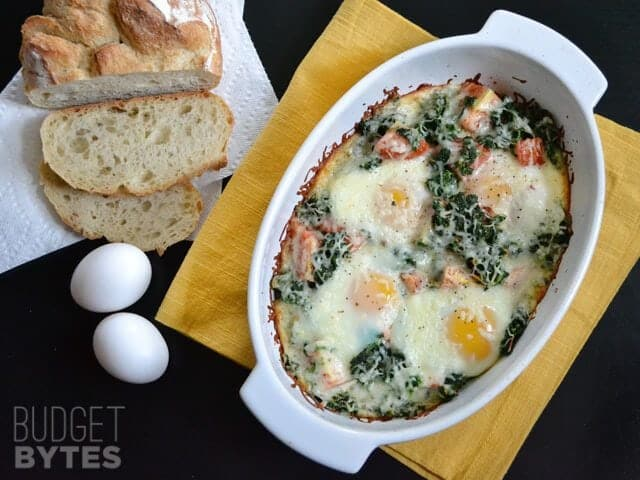 Top view of finished Baked Eggs with Spinach and Tomatoes, bread and whole eggs on the side