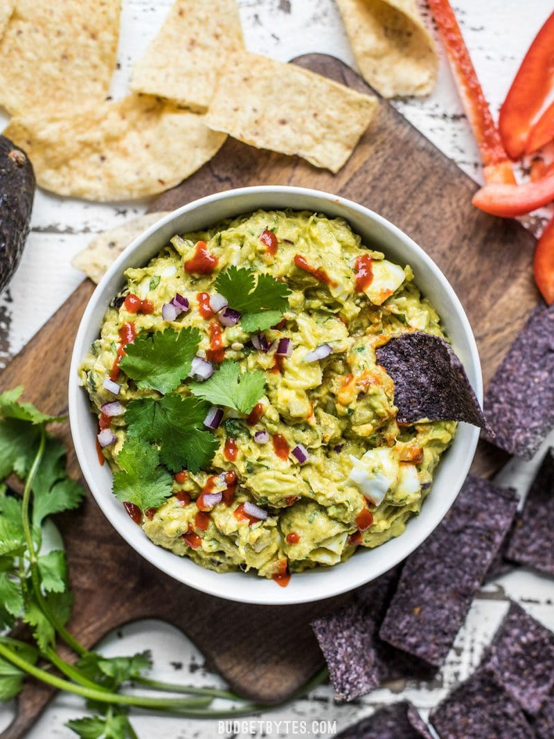 """Top view of a bowl of """"best ever avocado dip"""" with chips on the side"""