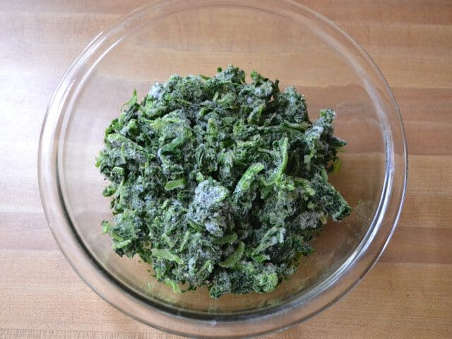 Spinach thawing in mixing bowl