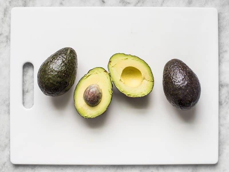 Three avocados, one cut in half