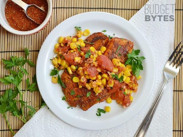 Top view of a plate of Blackened Tilapia with Corn salad on stop, small bowl of extra seasoning and fork on the side
