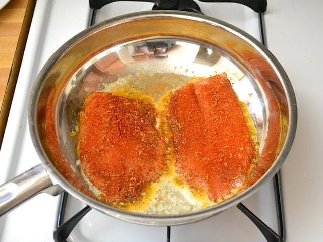 Two tilapia fillets cooking in skillet on stove top