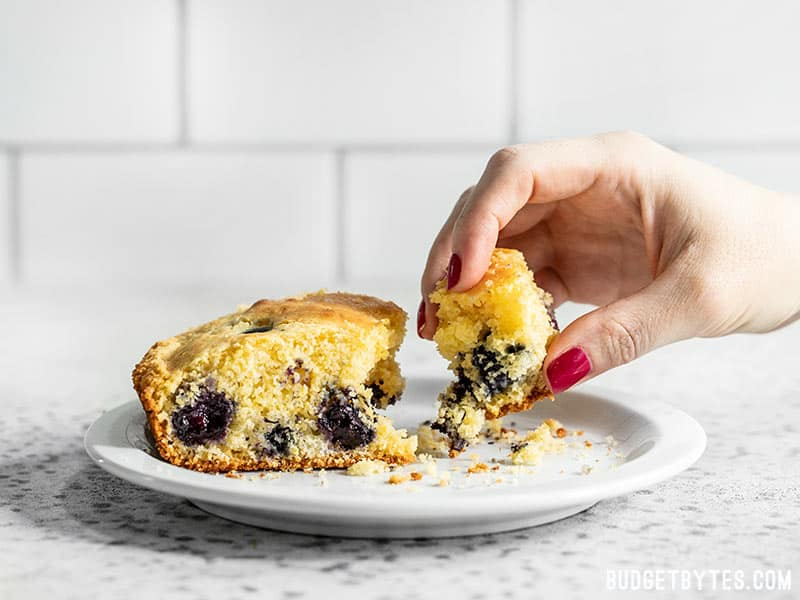 A hand taking a piece of Lemon Blueberry Cornbread from a plate.
