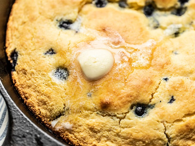 Close up of a pat of butter melting on the surface of Lemon Blueberry Cornbread