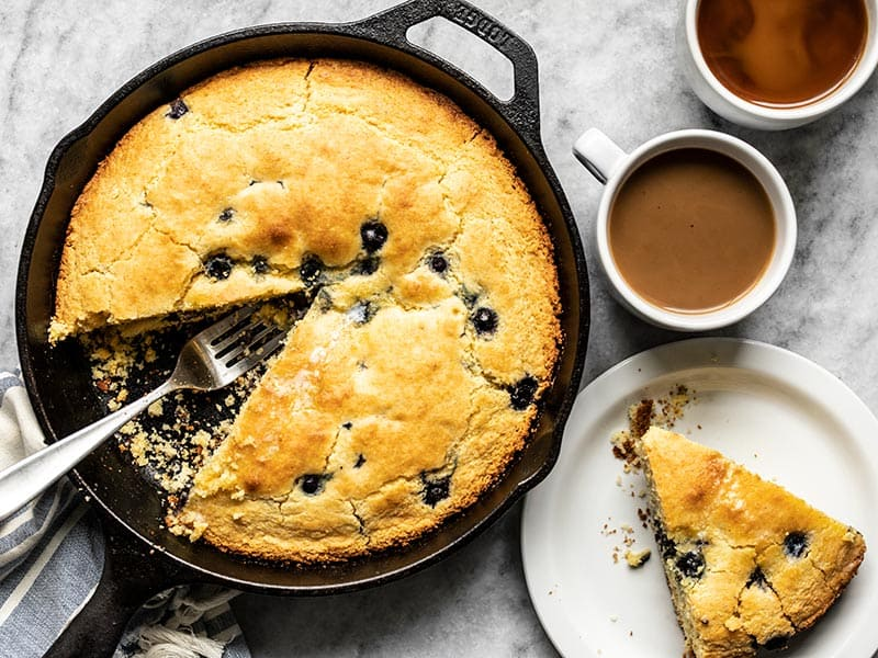 Lemon Blueberry Cornbread served on a plate next to the skillet and two mugs of coffee.