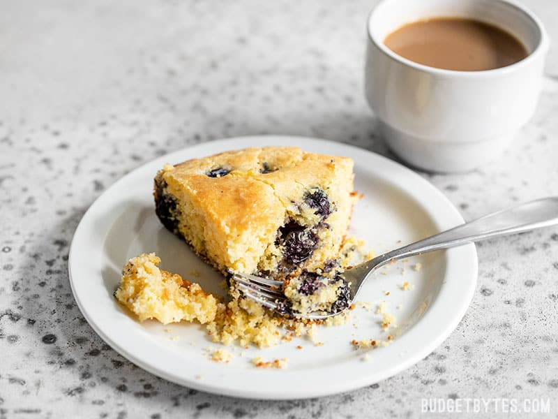 A slice of Lemon Blueberry Cornbread on a plate with a fork and cup of coffee in the background.