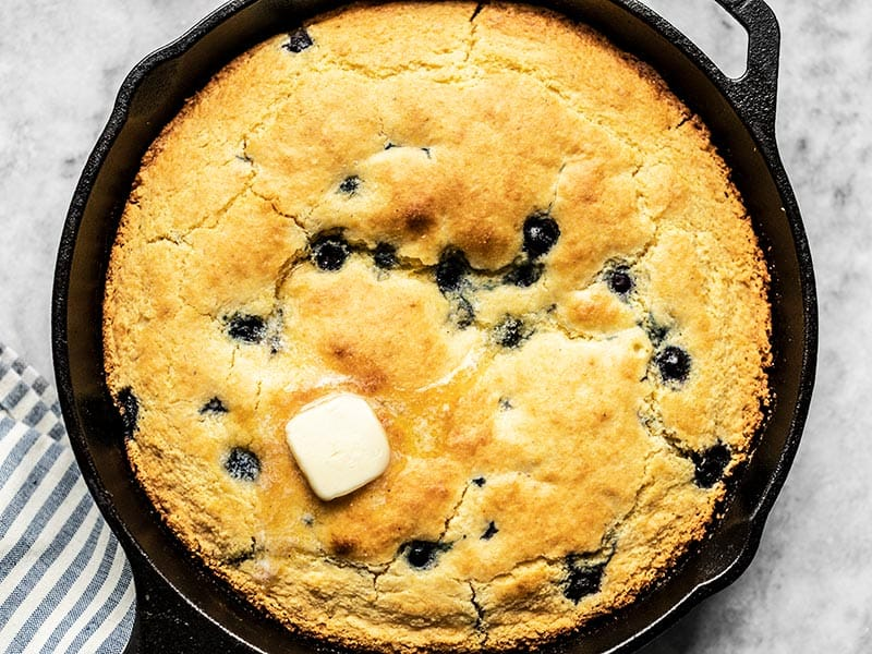 Close up of baked Lemon Blueberry Cornbread in the skillet with some butter melting on top.